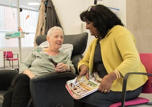 A woman chats to her friend while having chemotherapy